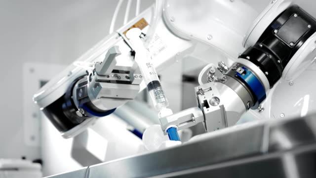 den innovativa armar av en robotarm gör en injektion av kemoterapi för en cancerpatient. ny teknik inom medicinen. två manipulatorer drar in medicinen i en spruta. farligt ämne injiceras. - sjukvårdsutrustning bildbanksvideor och videomaterial från bakom kulisserna