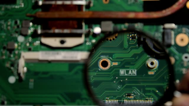 The inscription wlan on the motherboard of the laptop under a magnifying glass video