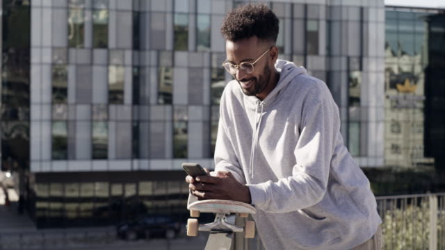 The internet is where I learn about new tricks 4k video footage a young skater using his cellphone while standing outdoors urban fashion stock videos & royalty-free footage