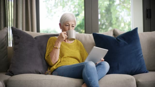 The internet's got her retirement entertainment covered 4k video footage of a senior woman using a digital tablet on the sofa at home mug stock videos & royalty-free footage