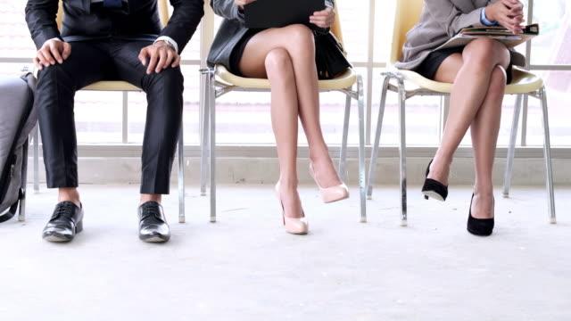 vídeos y material grabado en eventos de stock de la entrevista para el trabajo. los reclutas se aburren y disfrutan de los gadgets. jóvenes esperan entrevistas sentados en sillas en un edificio de oficinas. - rivalidad