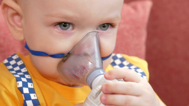 The kid himself holding a mask from an inhaler and breathes the medicine at home. Treats inflammation of the airways via nebulizer. Preventing asthma and cough video