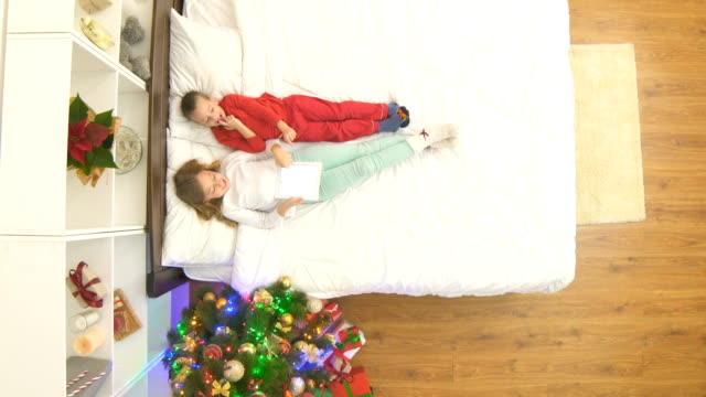 The kids with a tablet lay on the bed and take gifts. view from above