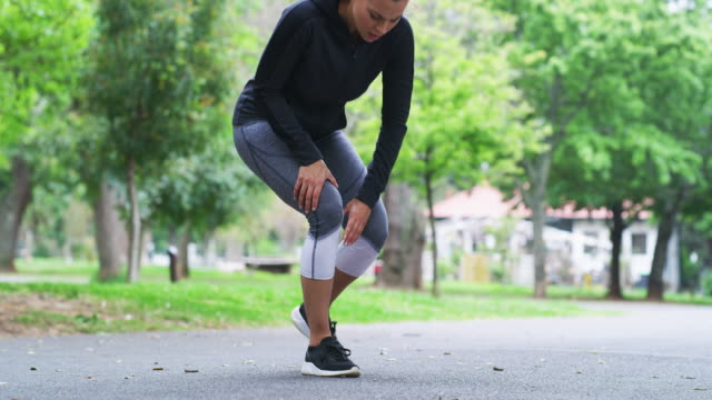 The knees always take the brunt 4k video footage of a fit young woman experiencing knee pain while running in the park knee stock videos & royalty-free footage