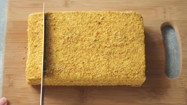 das messer schneidet einen rechteckigen honigkuchen in stücke. - rechteck stock-videos und b-roll-filmmaterial
