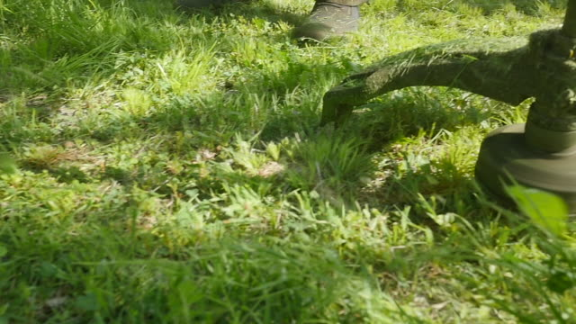 The Lawnmower Mows the Grass in Slow Motion The Lawnmower Mows the Grass in Slow Motion weeding stock videos & royalty-free footage