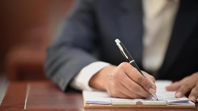 弁護士は法廷で事件記録を書くためにペンを持っている - 犯罪者点の映像素材/bロール