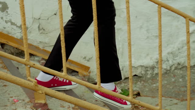 The legs of a man coming down the stairs in red sneakers and black pants. A man goes down the steps