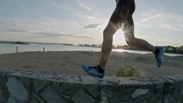 benen av en löpare som körs i parken vid solnedgången, närbild - tävlingsdistans bildbanksvideor och videomaterial från bakom kulisserna