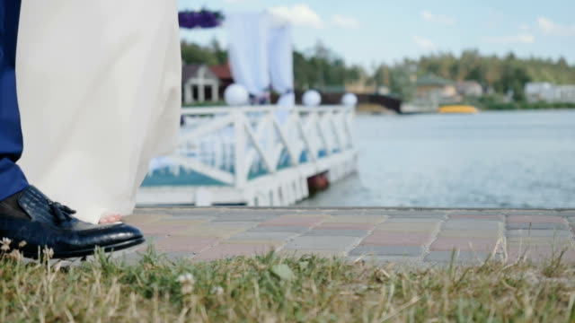 The legs of bride and groom are going on river background video
