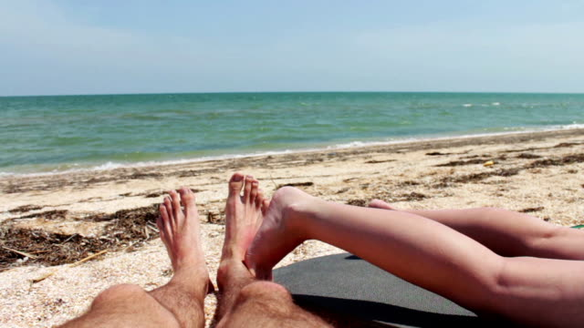The legs of two people are sunbathe on the beach by the sea video