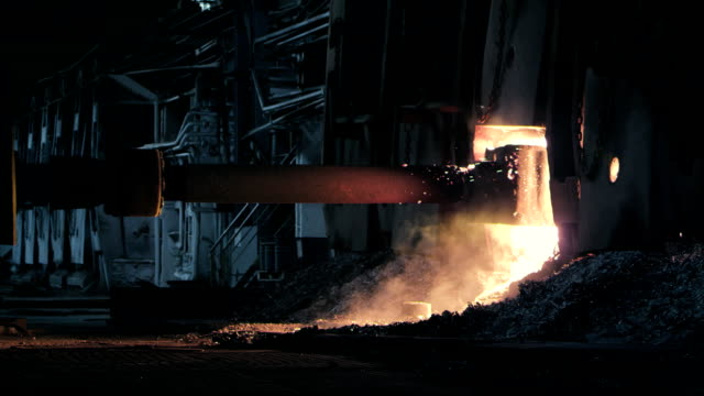 the liquid metal is being got out of a huge steel furnace - ferro video stock e b–roll