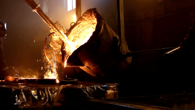 sıvı metal kalıplara dökülür. fabrikada metalin erime. - demir stok videoları ve detay görüntü çekimi