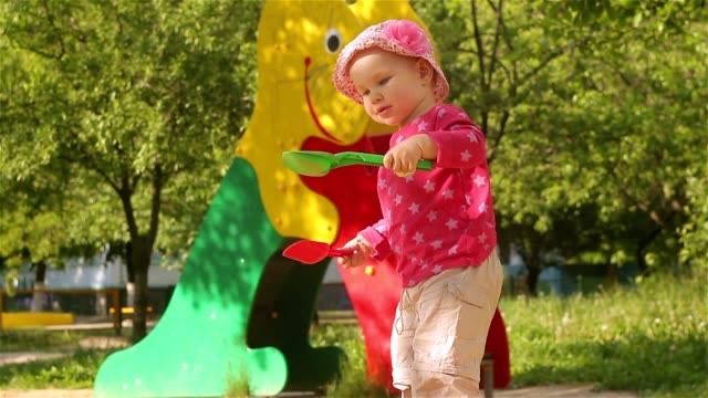 The little baby girl plays in the sandbox. video