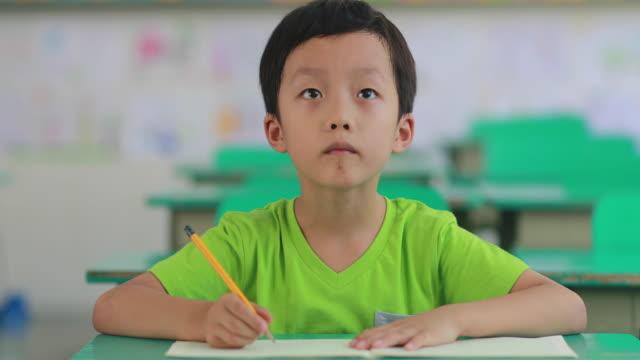 vídeos de stock, filmes e b-roll de o menino está em classe - aula de redação