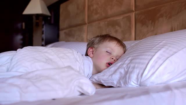 den lilla pojken sover i sängen. - cosy pillows mother child bildbanksvideor och videomaterial från bakom kulisserna