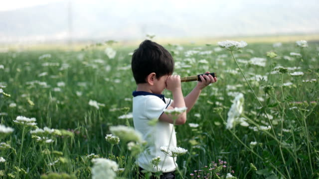 The little boy young researcher looks up and exploring with binoculars