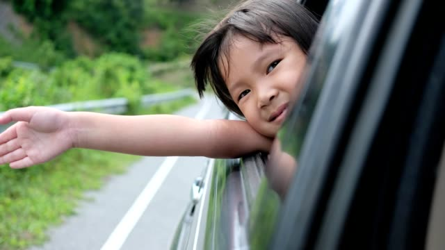 the little child feels refreshed with the tourist atmosphere by car. - viaggio in macchina video stock e b–roll