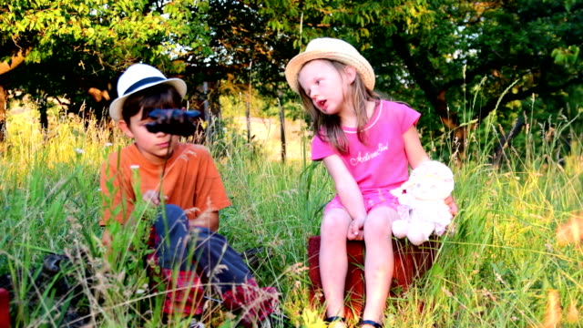 The little children spend the summer time in the garden. Children spend their summer holiday vacation in the garden video