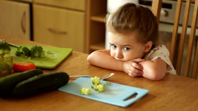 vídeos de stock e filmes b-roll de the little girl angrily looks at the broccoli. not hungry. protest, lack of appetite. - brócolo
