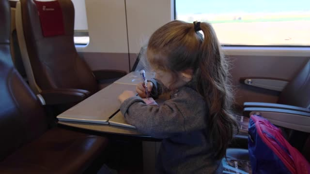 The little girl drawing in her notepad in the train.
