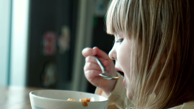 The little girl eats at a table The little girl eats porridge hungry child stock videos & royalty-free footage