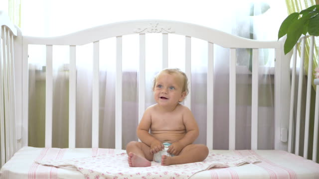 The little girl is happy and jumps on the bed. The little girl is happy and jumps on the bed. Baby sitting on a baby cot and laughs. Little girl sitting in a baby cot. The baby looks aside. rocking chair stock videos & royalty-free footage