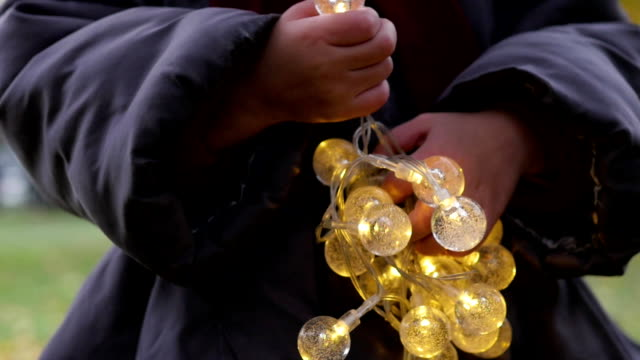 the little girl is holding a garland in her hands. hanging on a tree light bulb video