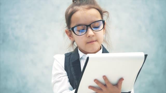 vidéos et rushes de la petite fille est sur un fond gris. pendant ce temps, il tient le dossier noir et scanne les feuilles. habillé comme une femme d'affaires. copiez l'espace. - bloc note