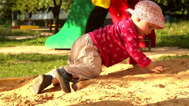 The little girl plays in the sandbox. video
