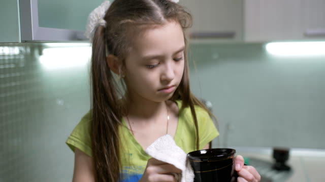 The little girl wipes her washed Cup in the kitchen. The little Girl in the kitchen wiping the Cup after washing it. chores stock videos & royalty-free footage