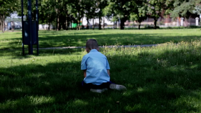 The little sad boy in the blue shirt was lost in the park and sitting on the grass alone. Boy with sad eyes and a frightened face is turning around and offended looking at the camera. autism stock videos & royalty-free footage