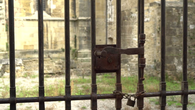 The lock on the ancient rusty metal gate. Behind the fence are the ruins