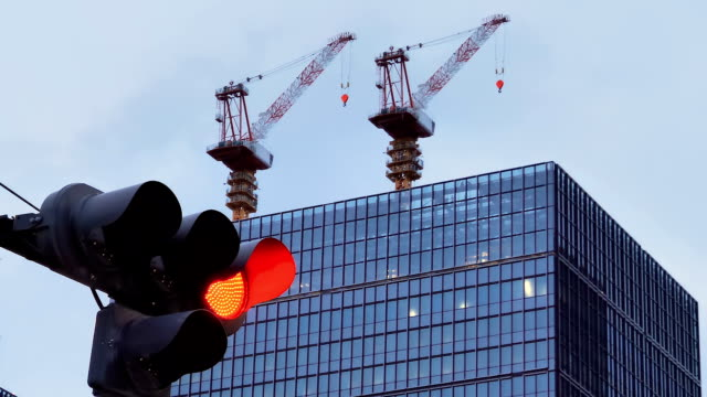 the look of the two tall cranes on the back of the building in japan - segnale per macchine e pedoni video stock e b–roll