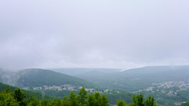 the low clouds and rain in the pocono mountains over jim thorpe town, pennsylvania, carbon county. timelapse-style accelerated mobile video. - горы поконо стоковые видео и кадры b-roll