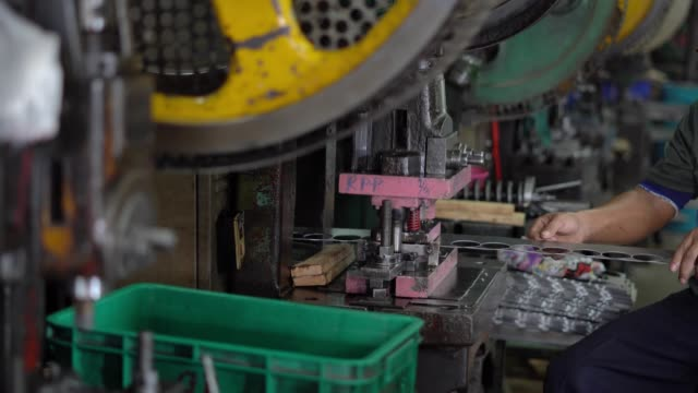 The machine is working by stamping a circle from a long steel plate, controlled by the worker and he has no safety protection. The machine is working by stamping a circle from a long steel plate, controlled by the worker and he has no safety protection. stamping feet stock videos & royalty-free footage