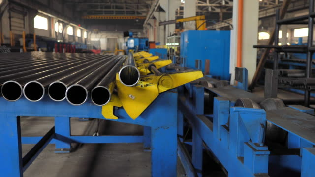 the machine loads a metal pipe to the production line. - acciaio inossidabile video stock e b–roll