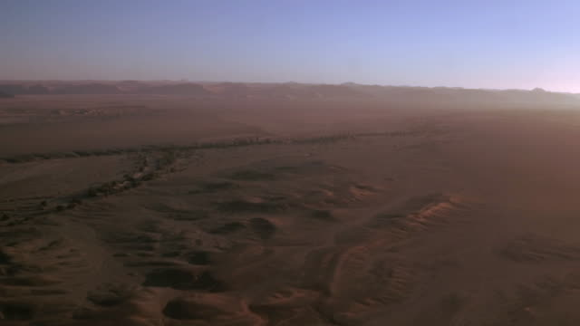 The majestic sand dunes of Sossusvlei A wide aerial shot with a drone from above, showing the incredible sand dunes at the horizon. The sun is setting and is giving the landscape that extra glow. horizon over land stock videos & royalty-free footage