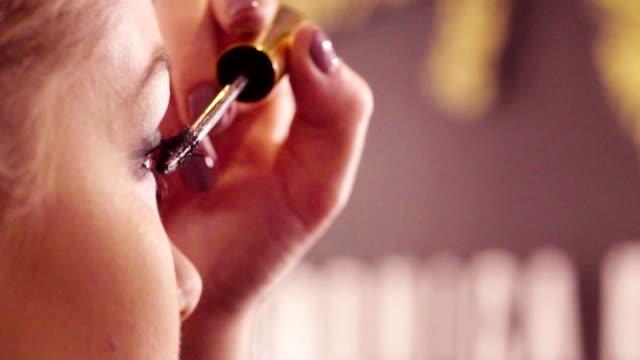 the makeup artist applying mascara - posizione corretta video stock e b–roll