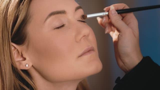 vidéos et rushes de le maquilleur met vif ombre à paupières sur les paupières, avec une brosse professionnelle sur le visage une modèle blonde caucasienne. gros plan, femme d'affaires de maquillage. slow motion - pinceau à maquillage