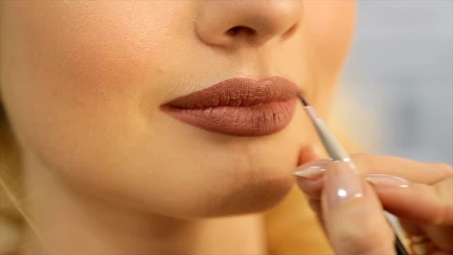 die visagistin setzt auf die lippen des modells einen hellen lippenstift - lippenstift stock-videos und b-roll-filmmaterial