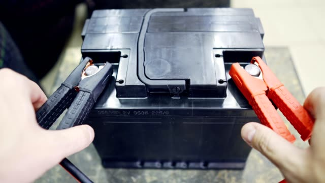 The male hand connects the terminals to the car's batteries. A man throws and removes the terminals on the battery