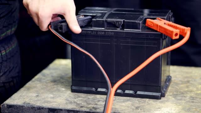 stockvideo's en b-roll-footage met de mannelijke hand verbindt de terminals met de batterijen van de auto. een man gooit en verwijdert de klemmen op de batterij - lood