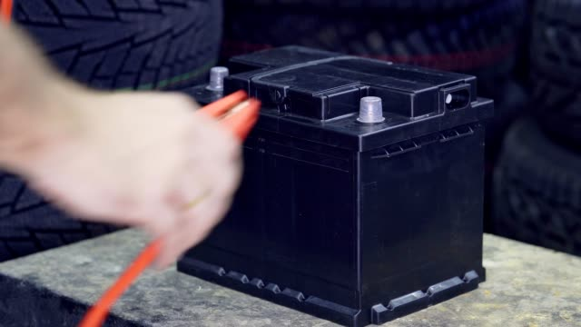 The male hand connects the terminals to the car's batteries. A man throws and removes the terminals on the battery.