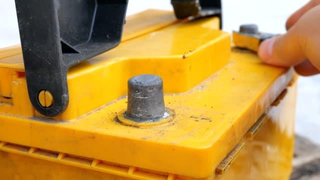 stockvideo's en b-roll-footage met de mannenhand loskoppelen de terminals aan de auto's batterijen voor het opladen - lood
