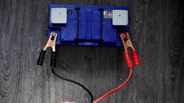 stockvideo's en b-roll-footage met de mannenhand loskoppelen de terminals aan de auto's batterijen op een houten achtergrond. - lood