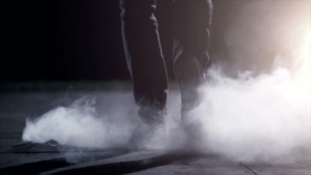 The male legs going near a smoke. evening night time, slow motion The male legs going near a smoke. evening night time, slow motion alley stock videos & royalty-free footage