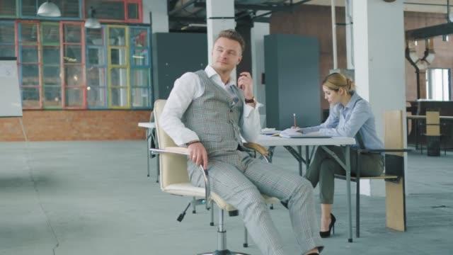 Der männliche Manager dreht einen Bürostuhl zu einer afroamerikanischen Kollegin, zwinkert und flirtet mit ihr. Sie mag es nicht. Business-Interieur im Stil eines Lofts. Büroleben – Video