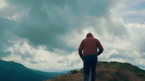 il maschio che corre sulla montagna e fa esercizio fisico. rallentatore - collina video stock e b–roll