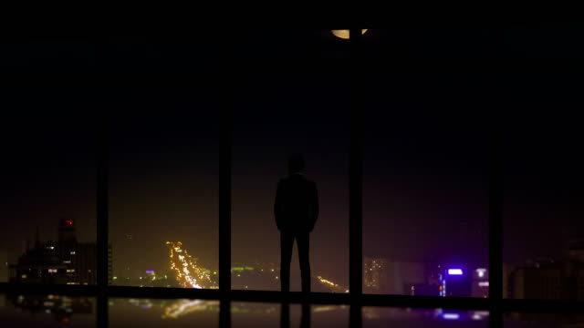 the male standing near panoramic windows on the night city background - man look sky scraper video stock e b–roll